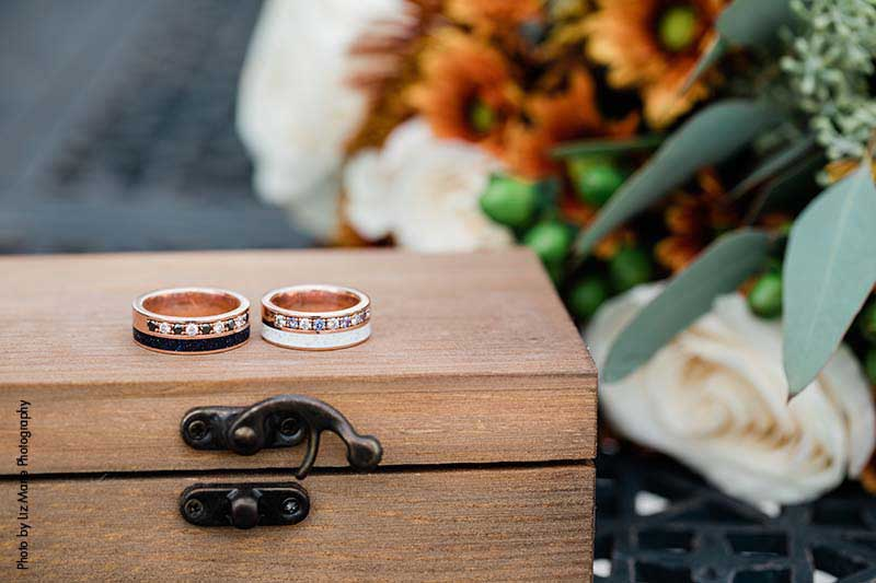 Rose gold groom's wedding rings, one with a black band and the other with a white band