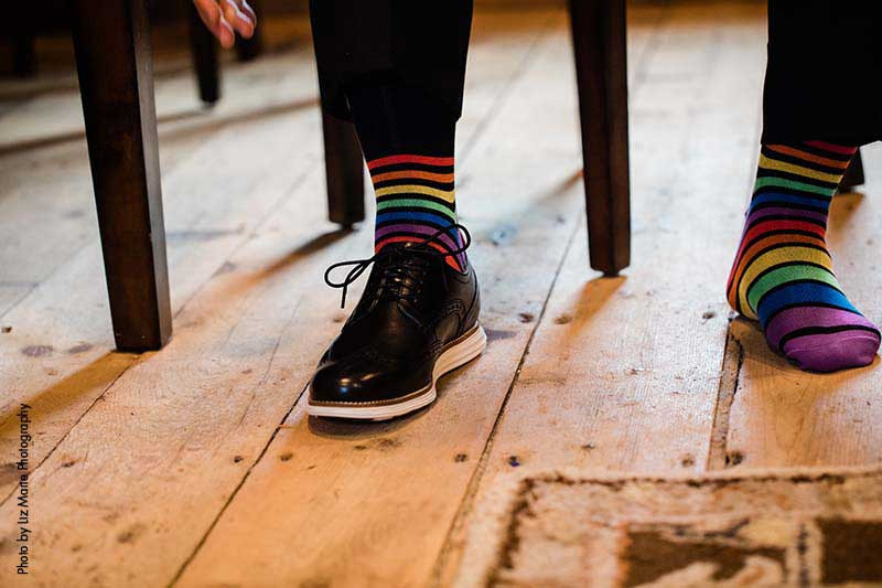 Groom wears rainbow striped socks for wedding