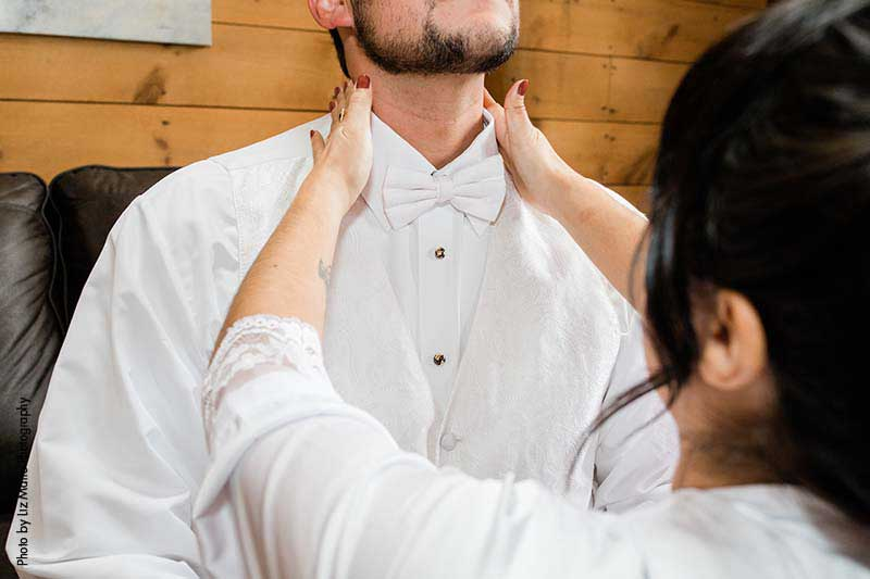 Mother helps groom put on white bowtie