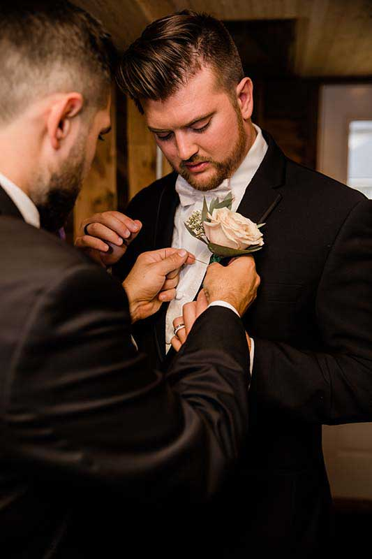 Groom puts on blush rose boutonnière