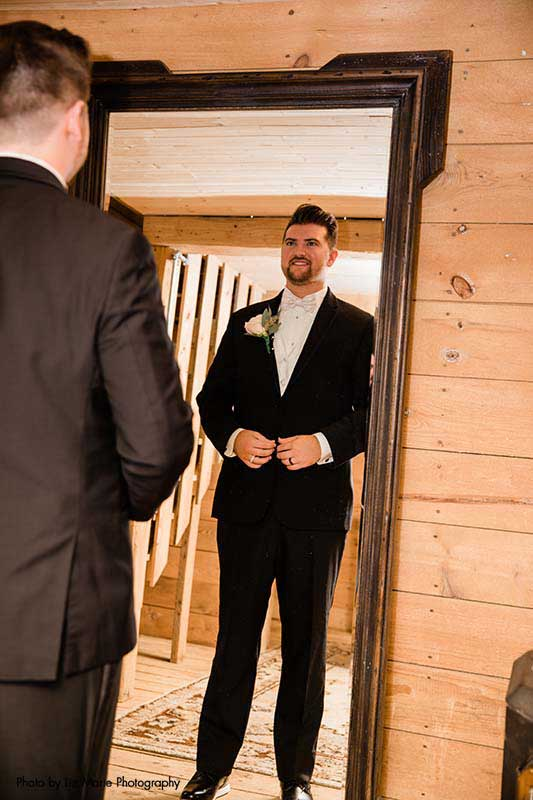 Groom looks at self in mirror in black tux before first look
