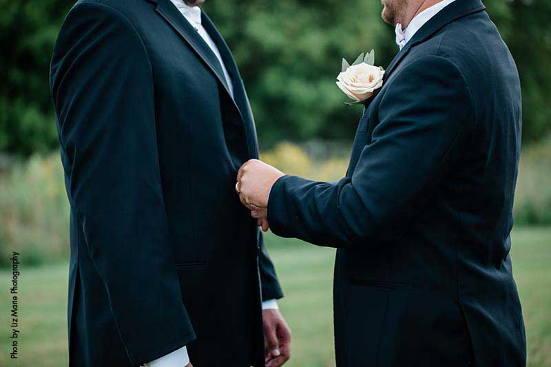 Grooms wear matching black tuxes