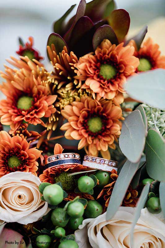 Groom's wedding rings sit in a floral bouquet