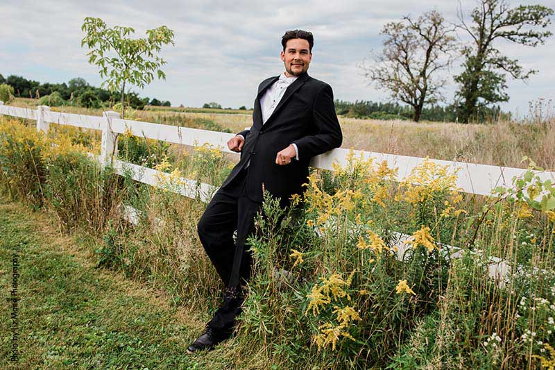 Groom in black tux leans up against white fence