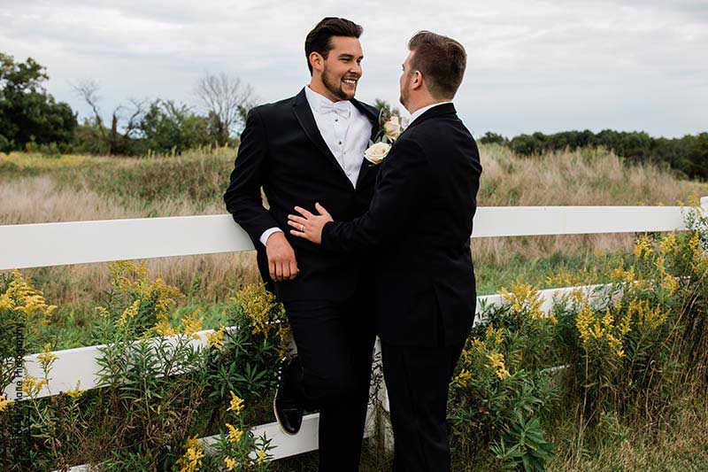 Two grooms pose against white fence