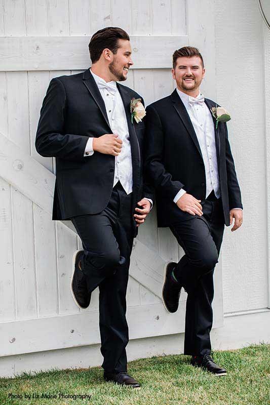 Grooms in sleek black tuxes lean up against modern white barn door