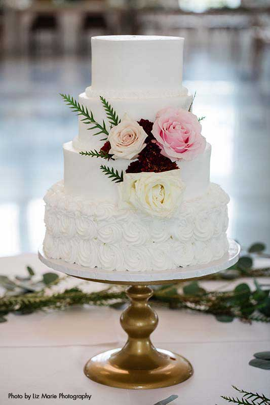 White wedding cake with four tiers and three multi-color roses and greenery