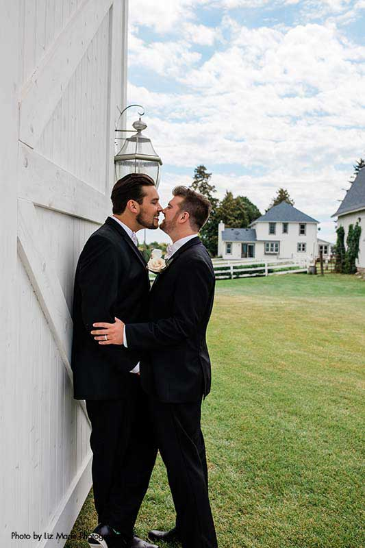 Grooms in black tuxes kiss outside modern barn wedding venue in Minnesota