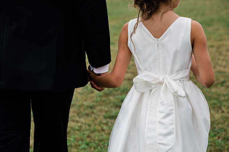 Groom holds hands with flower girl in white dress with bow