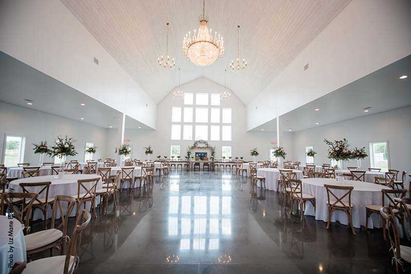 Modern barn wedding venue with white walls and ceiling and chandeliers