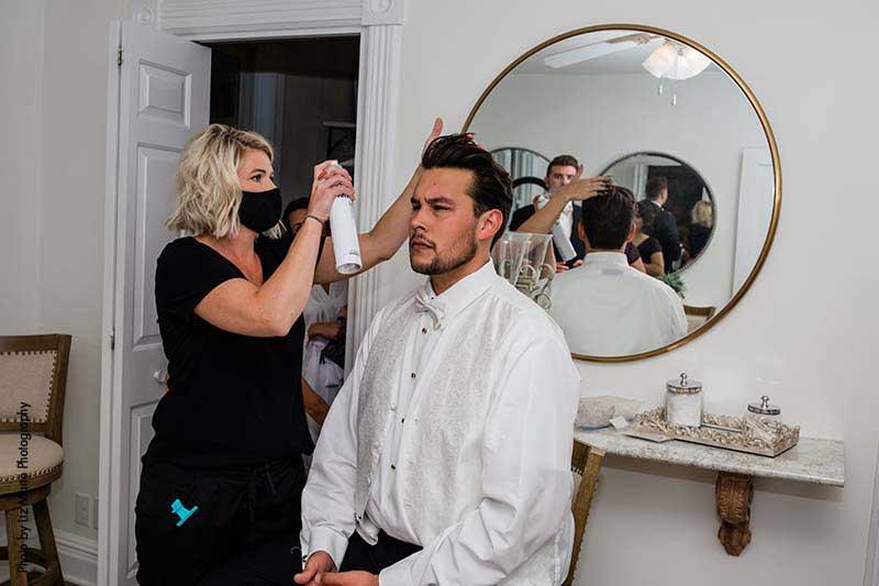 Groom gets hair styled before wedding