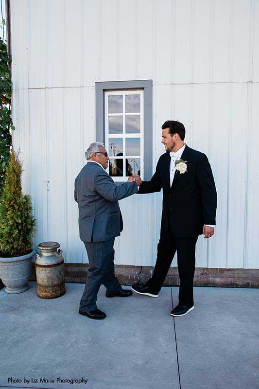 Groom in black tux does a handshake with father in gray suit