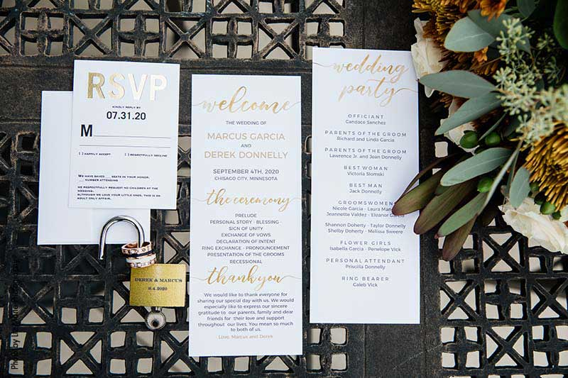 White wedding stationery with metallic gold and black lettering
