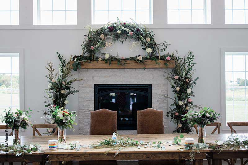 Fireplace at wedding venue with floral and greenery arch sit behind head table