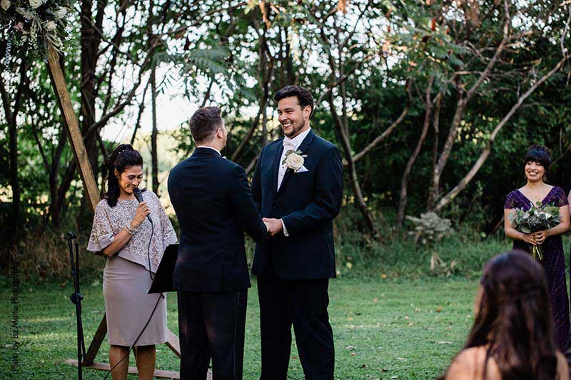 Two grooms share vows at same-sex outdoor wedding