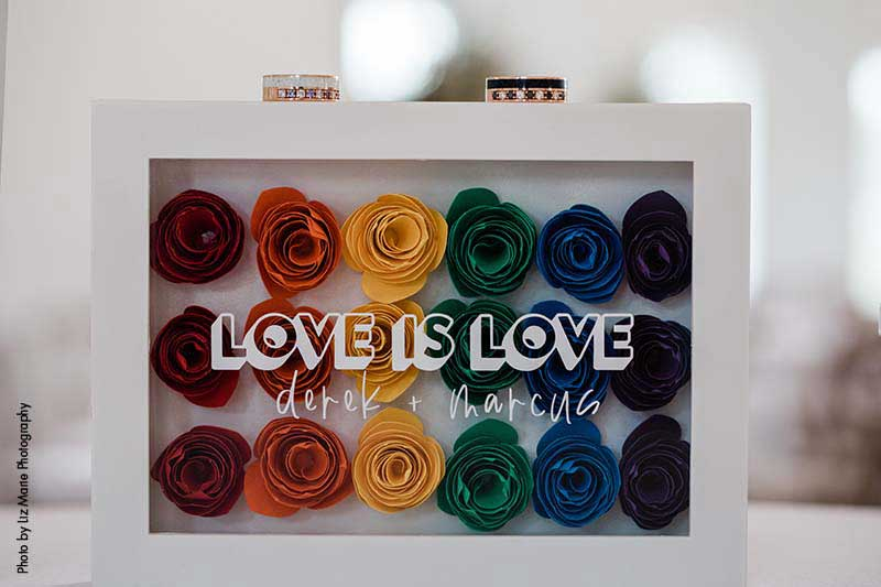 """Rainbow paper flower display that says """"Love is Love"""""""