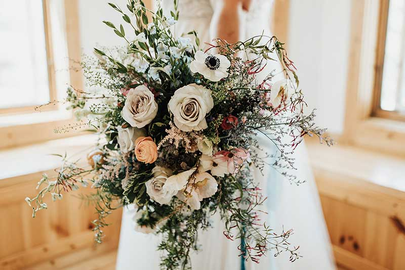 Moody bridal bouquet with anemone, roses, greenery
