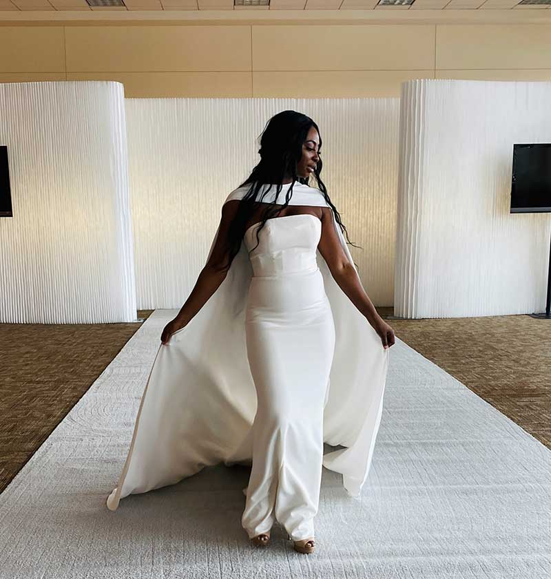 Simple crepe wedding dress with a long crepe cape on bridal fashion show runway