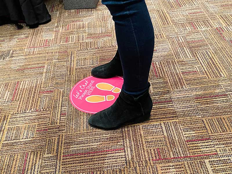 Pink social distancing floor sign