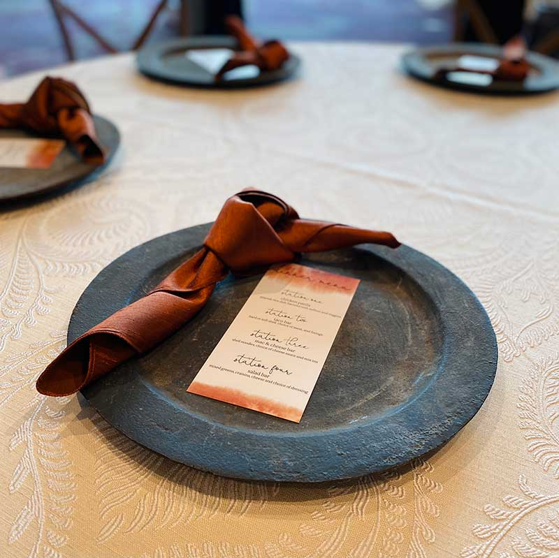 Dark orange napkin on top of slate black charger for wedding