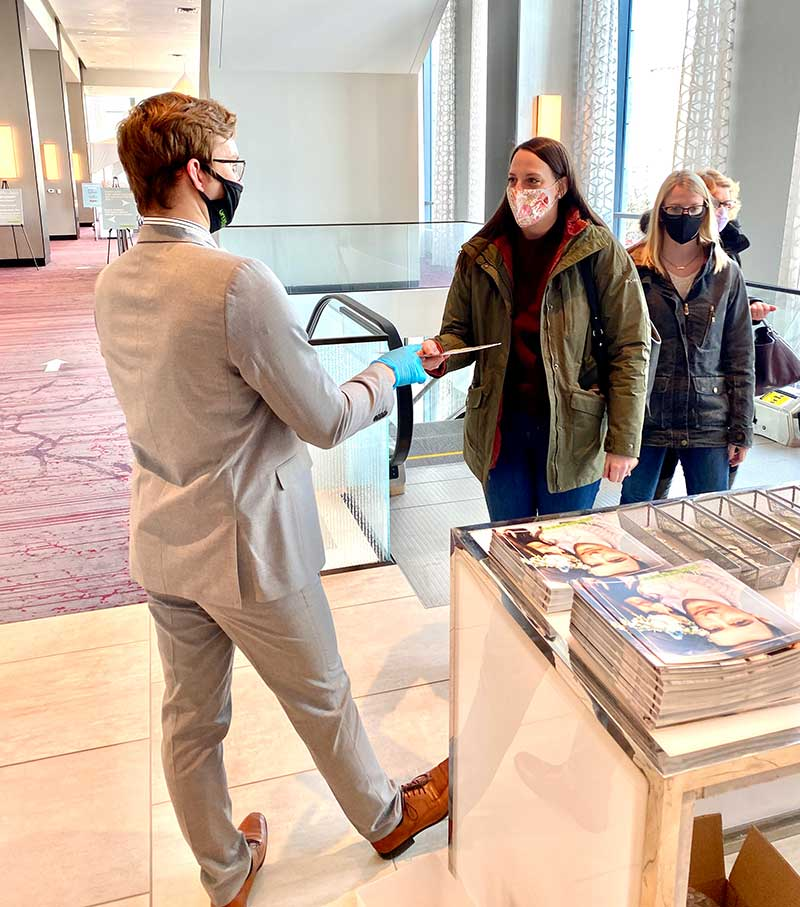 Employee hands out programs at UNVEILED Rochester 2021 bridal show