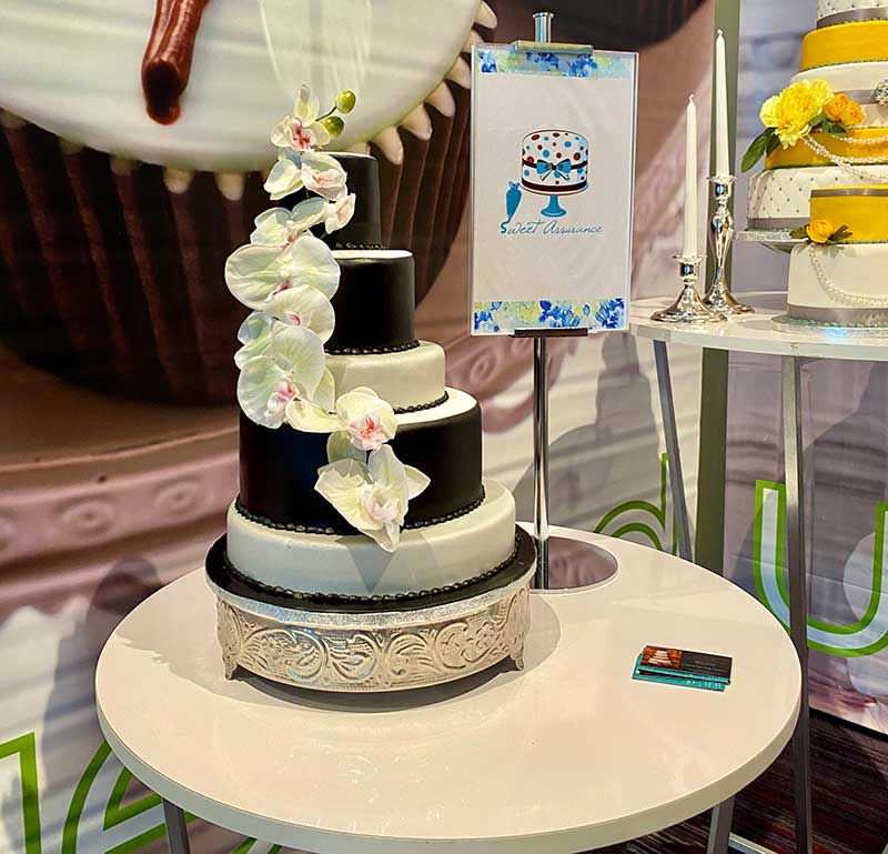 Black and white tiered wedding cake with orchids