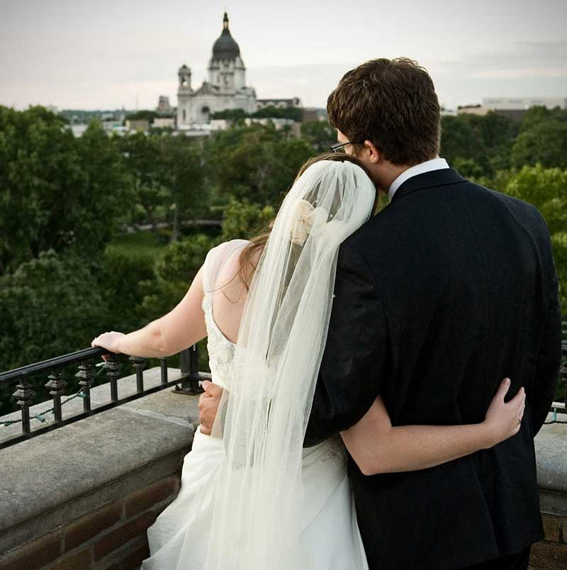 Couple looks over balcony at Minneapolis wedding venue