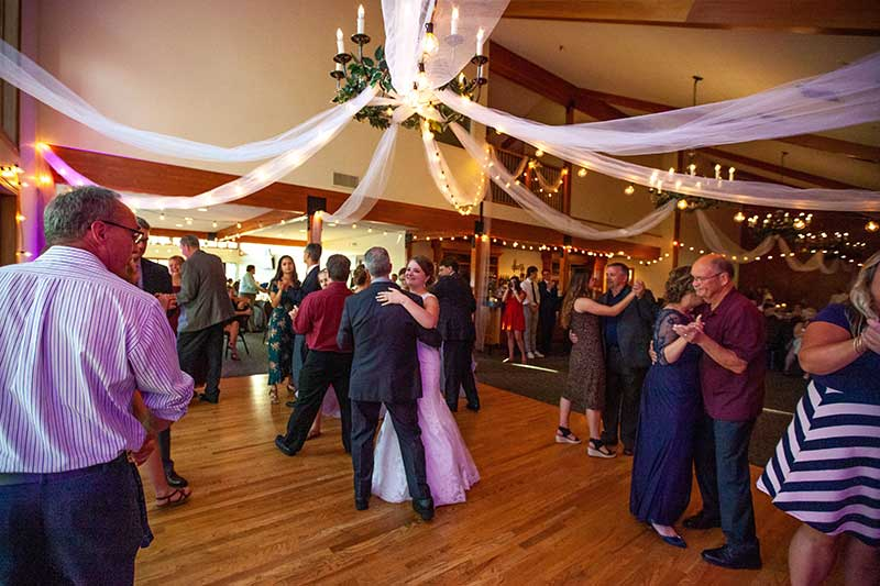 Bride and groom dance at golf course wedding reception