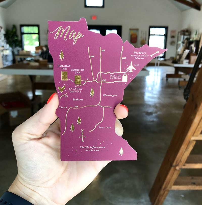 Maroon and gold wedding invite in the shape of Minnesota