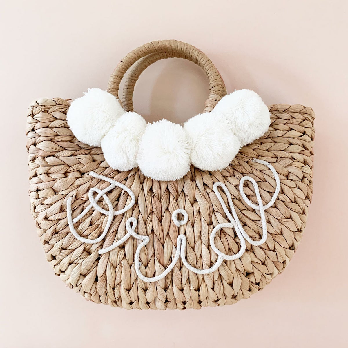 """Woven bag that says """"Bride"""" with white pom balls"""