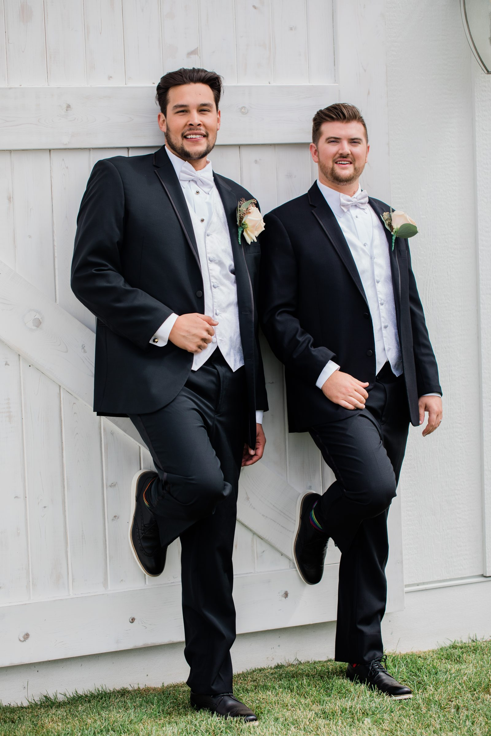 Grooms stand in front of barn at Minnesota wedding