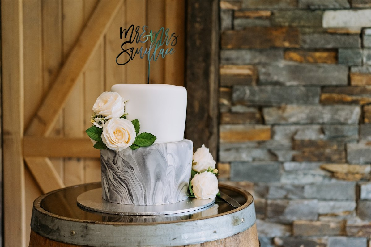 Marble gray and white wedding cake with peach-colored flowers