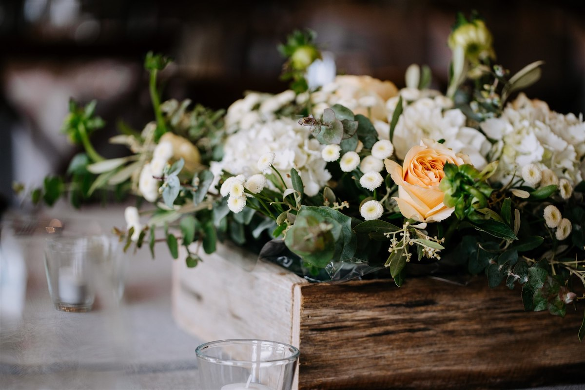 Peach, greenery, and white flowers sit in wooden box