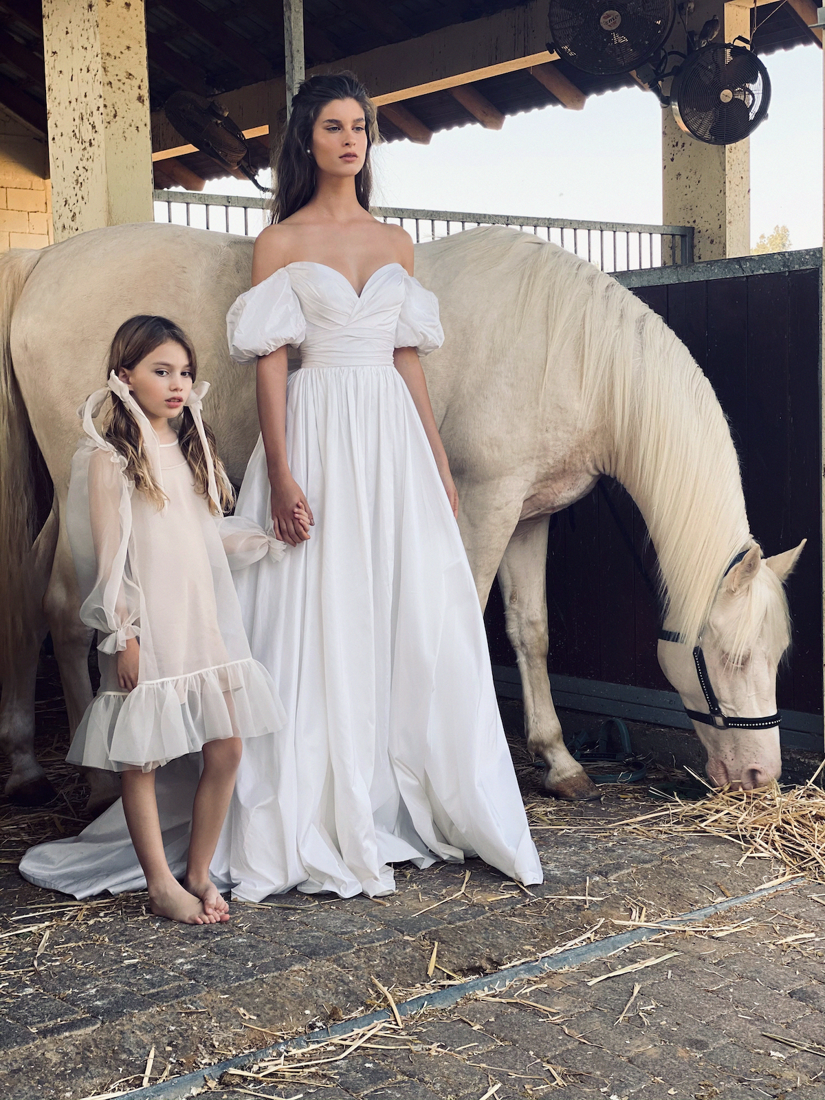 Off-the-shoulder puffy sleeve wedding dress on bride with flower girl