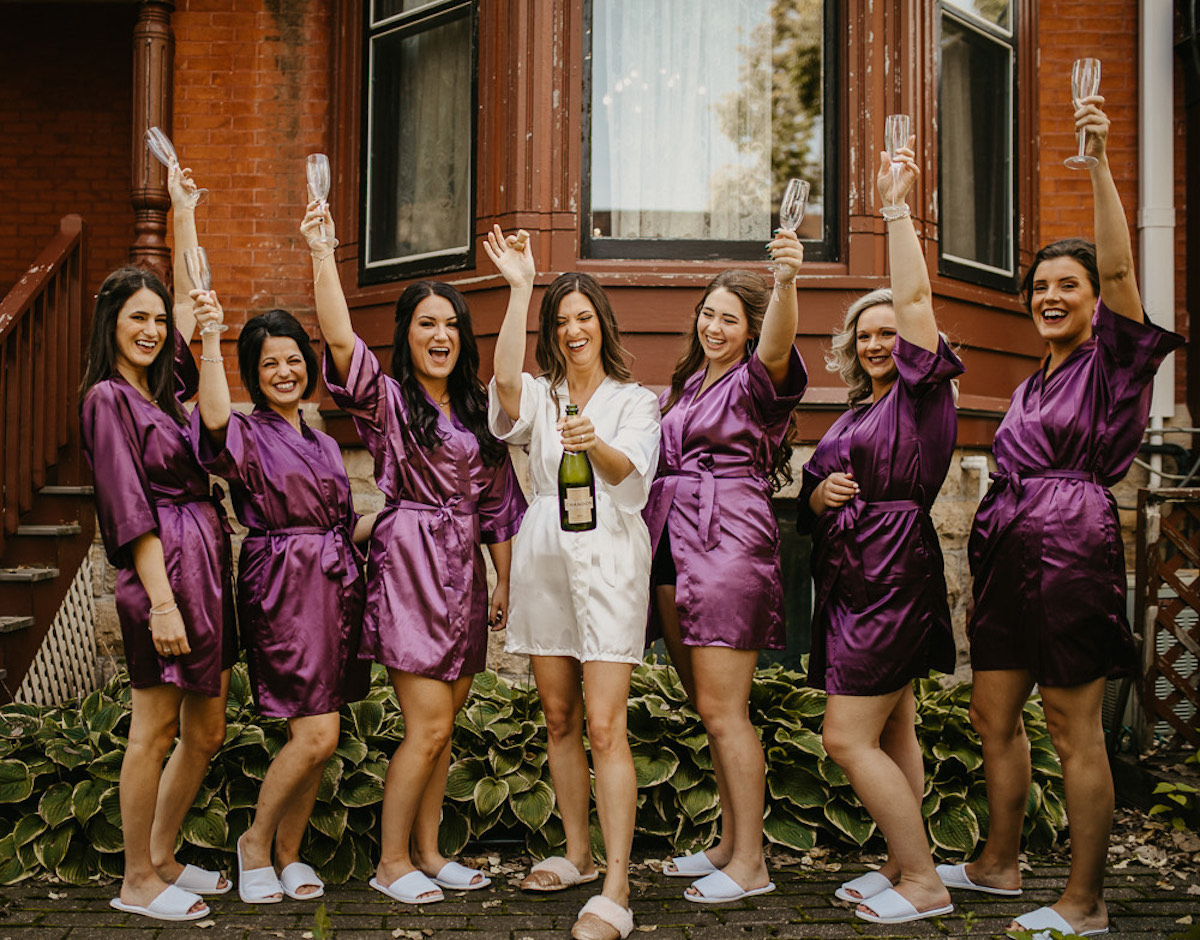 Bride and bridesmaids pop champagne