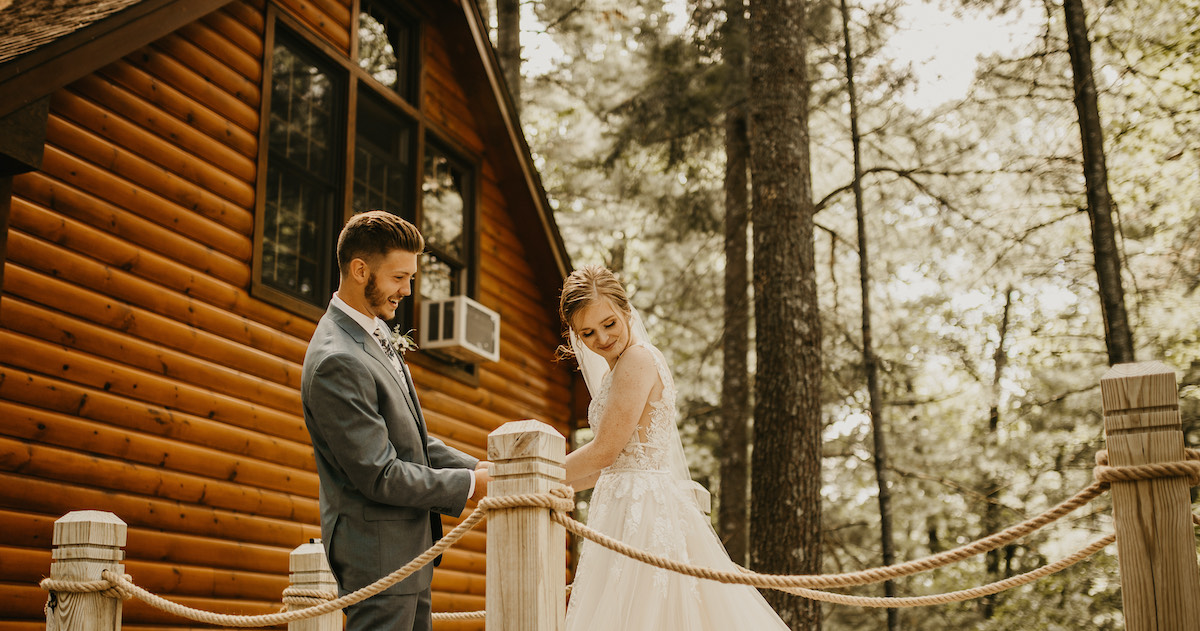 Bride and groom share first look before wedding ceremony in woods