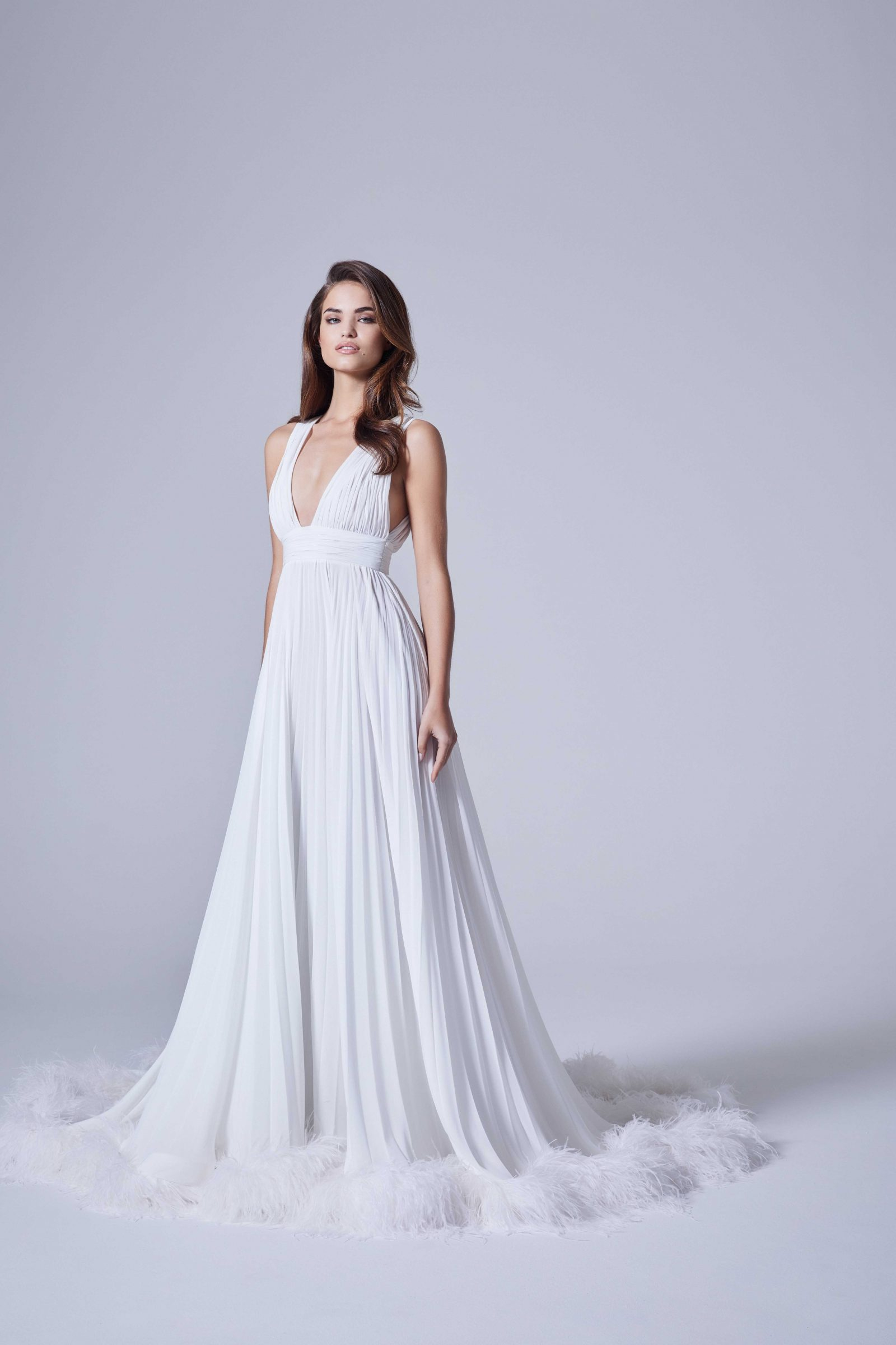 Deep V flowly bridal gown with feathers on bottom by Nicole + Felicia Couture