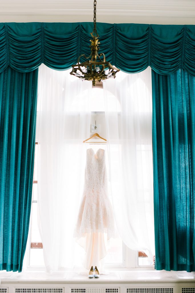 Strapless white dress hangs from window with tall teal drapes