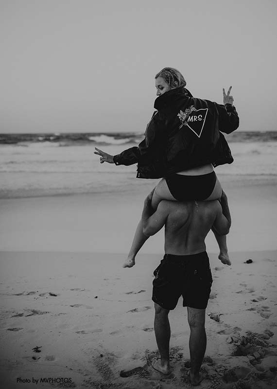 Bride sits on groom's shoulders as they walk on the beach