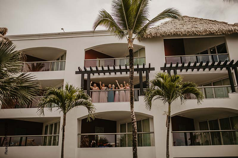 Bridesmaids stand on balcony at the Hard Rock Hotel Punta Cana