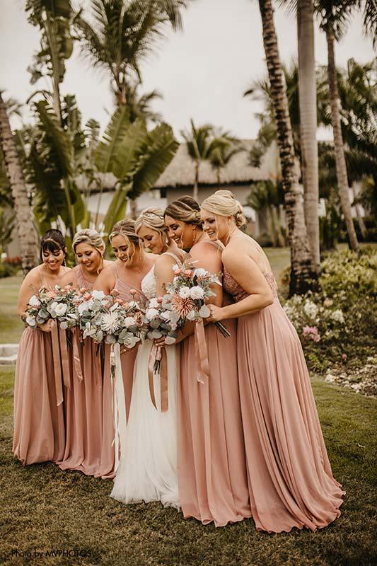 Bridesmaids in blush wedding dresses at tropical wedding