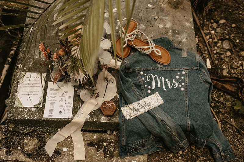 """Bridal """"Mrs"""" jean jacket with dried floral, simple wedding invitations, and garter"""