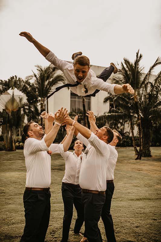 Groomsmen toss groom in the air