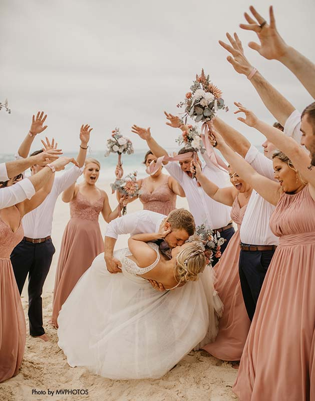 Wedding party celebrates bride and groom on beach