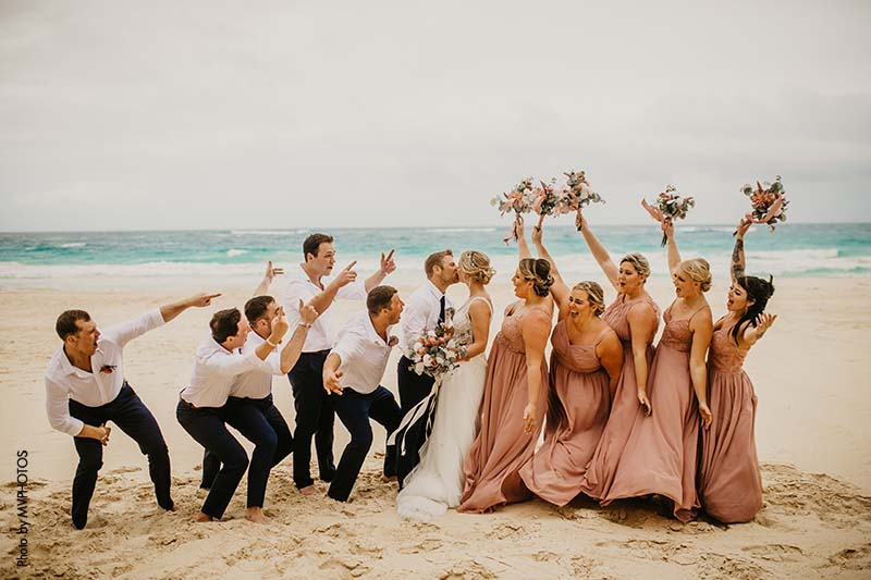 Wedding party celebrates bride and groom on the beach