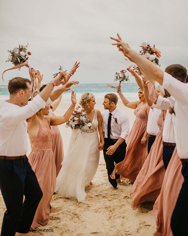 Bride and groom celebrate with bridal party at beachside wedding