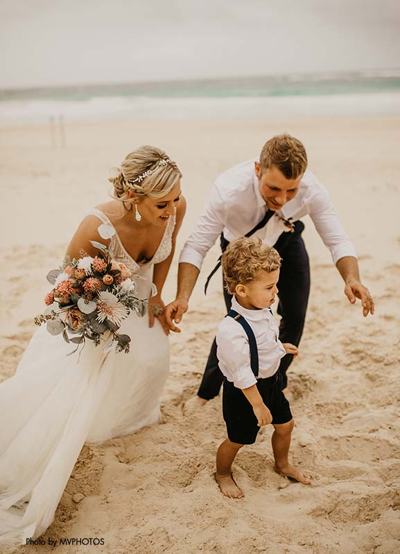 Bride and groom pose with ring bearer at destination wedding