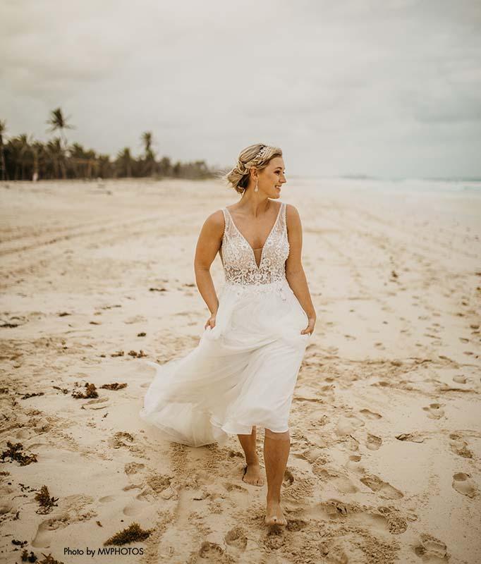 Bride walks along water after her beachside wedding in a flowy destination wedding dress