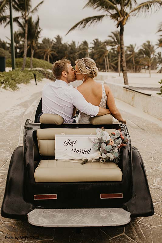 """Bride and groom drive away in car with """"just married"""" sign"""