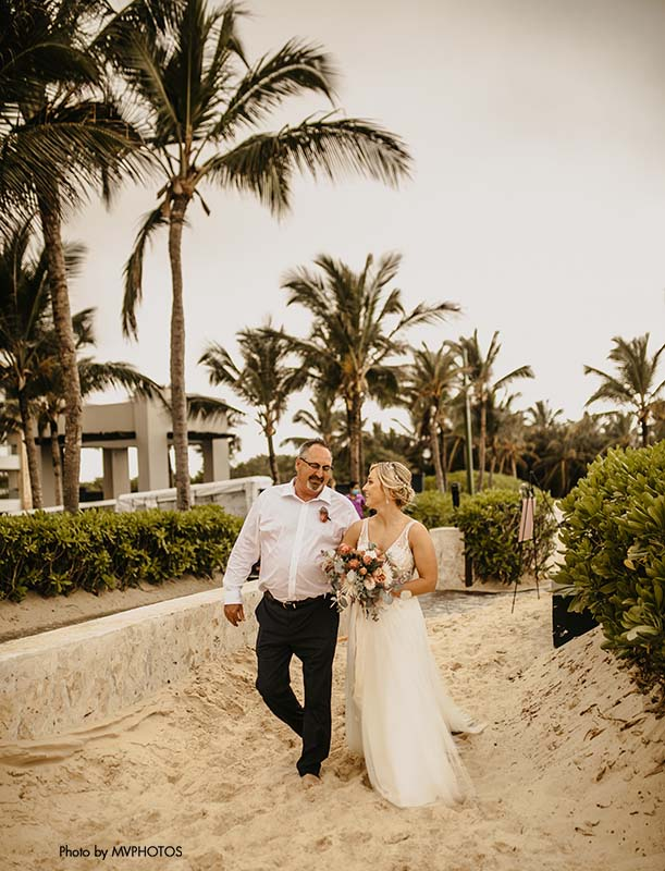Bride walks down the aisle in the sand with father